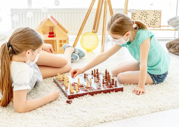 Beautiful girls playing chess during quarantine