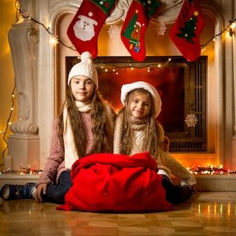 선물에 대 한 큰 빨간 가방 벽난로 옆에 앉아 아름 다운 여자