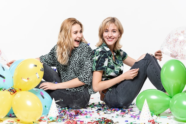 Beautiful girls  surrounded by confetti and balloons