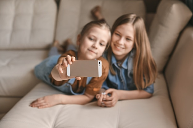 Beautiful girls take selfies on their phone while lying on sofa. sisters take a break from homework and take photos during quarantine