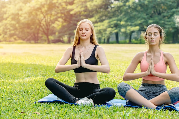 Beautiful girls teen friend do yoga for healthy in green park holiday sitting hand lotus eyes closed concentration posture.