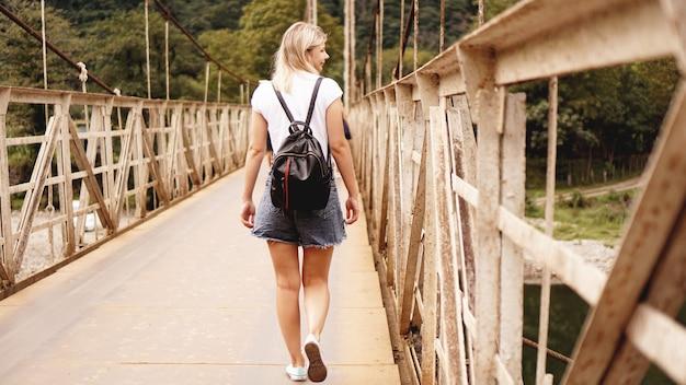 여행하는 아름다운 소녀들, 아름다운 산의 경치를 즐기면서 다리 위를 걷는다