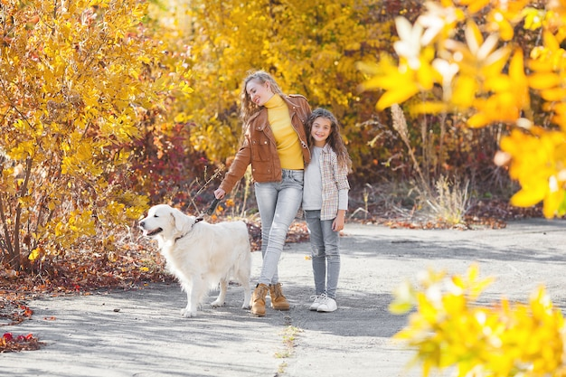 Beautiful girls with golden retriever. two sisters outdoors having fun.pet owners in autumn.
