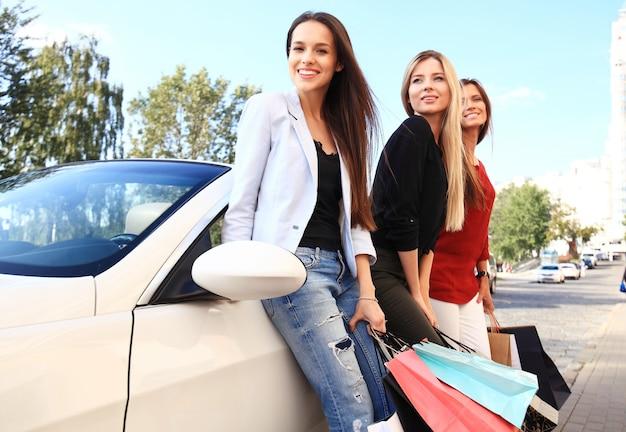 쇼핑 가방을 가진 아름다운 소녀는 구매를 논의하고 차에 기대어 웃고 있습니다.