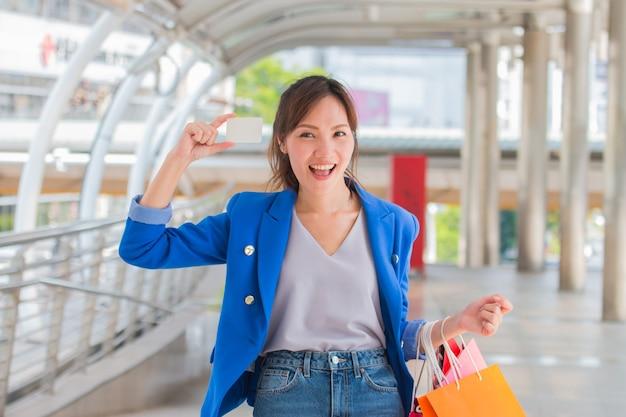 ショッピングバッグを持つ美しい女の子は、モールで買い物をしながら笑っています