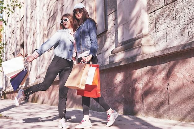 ショッピングモールで歩いて買い物袋を持つ美しい女の子。
