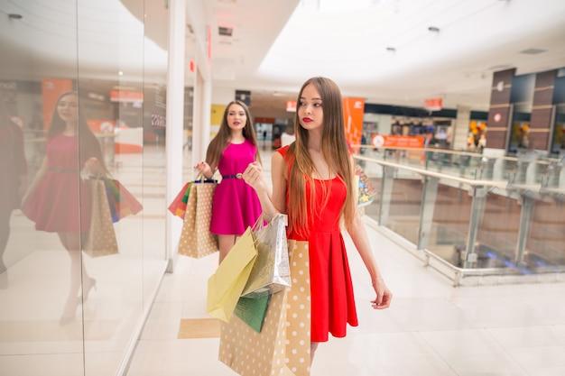 ショッピングモールで歩いて買い物袋を持つ美しい女の子