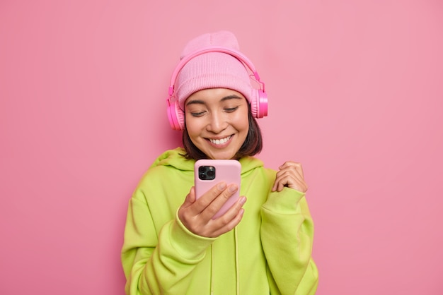 Beautiful glad asian female teenager looks happily at smartphone listens music via headphones enjoys favorite playlist wears hat and green sweatshirt isolated over pink wall
