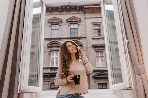 Beautiful glad white lady relaxing in morning with cup of hot beverage