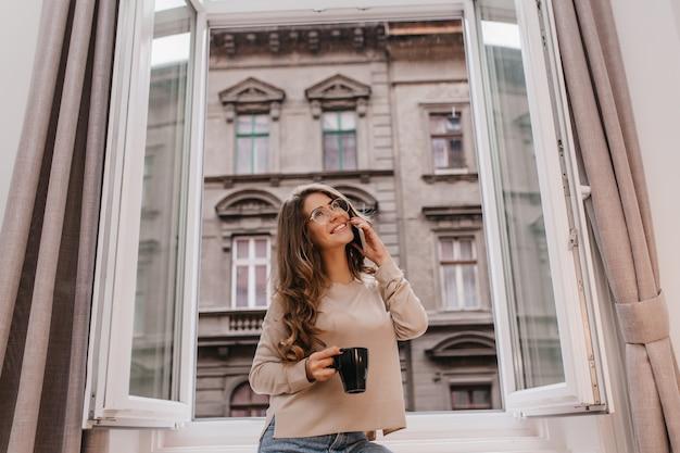 Bella signora bianca felice che si rilassa al mattino con una tazza di bevanda calda