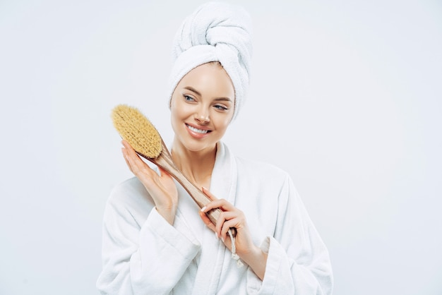 Beautiful glad woman with healthy skin and toothy smile holds wooden massage brush