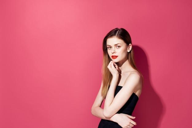 美しいグラマー女性赤い唇の装飾黒いドレスピンクの壁。