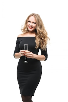 Beautiful glamorous girl with red lips in smart black dress  a glass of champagne isolated on white background looking at the camera