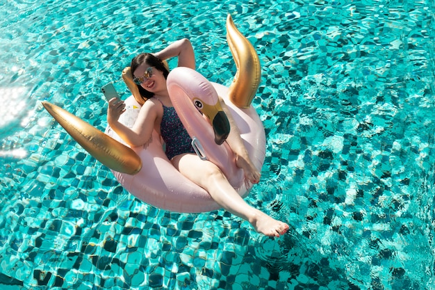 Beautiful glamorous young brunette woman taking a selfie on a fink and gold flamingo