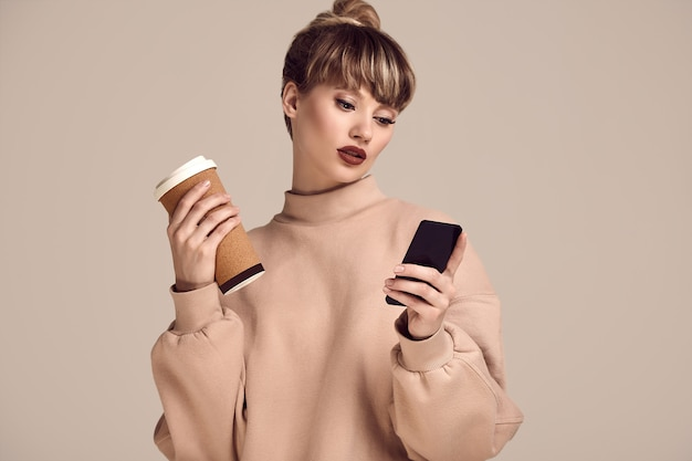 Beautiful glamour blond hipster woman with cup of coffee and phone