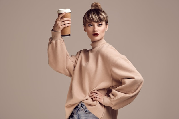 Beautiful glamour blond hipster woman with cup of coffee