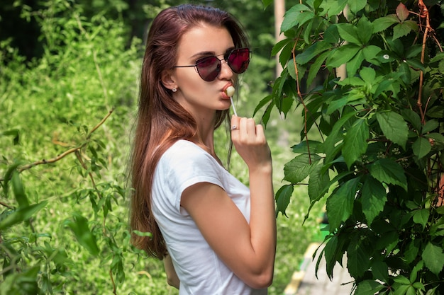 Beautiful glamour girl in bright glasses licks a lollipop and looks into the camera close-up
