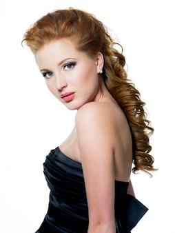 白で隔離され、明るいメイクで美しいグラマー赤髪の女性。プロフィールの肖像画