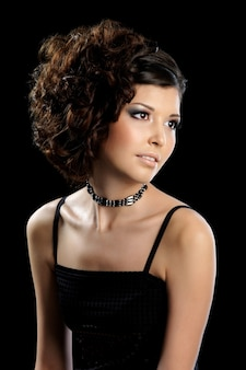Beautiful glamour woman with curly hairstyle and bright make-up isolated on black wall