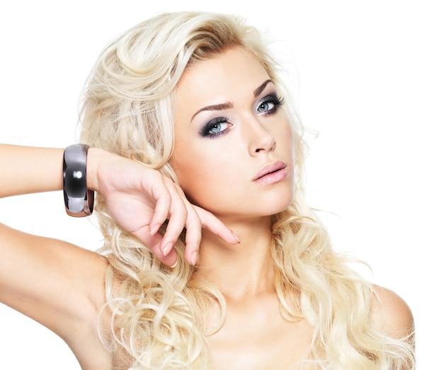 顔に手を持つ美しい魅力的な女性-白で隔離