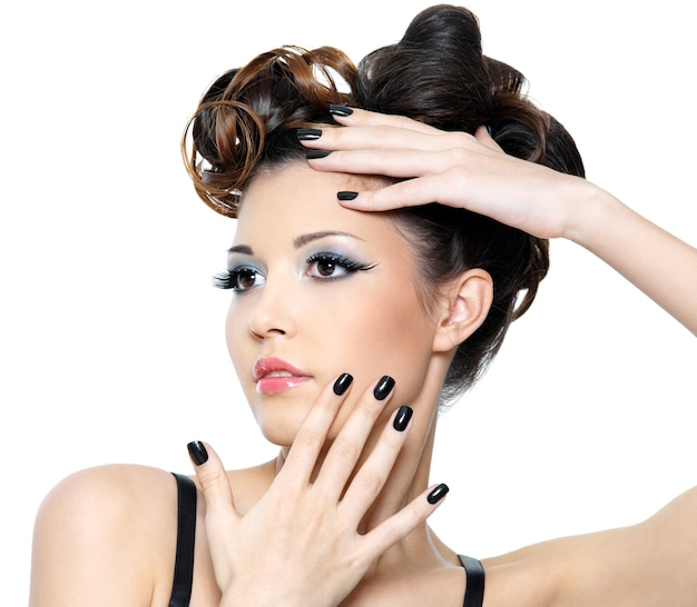 Beautiful glamour woman with stylish hairstyle and black nails. fashion eye make-up