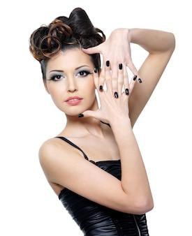 Bella donna glamour con acconciatura alla moda e unghie nere. trucco occhi alla moda