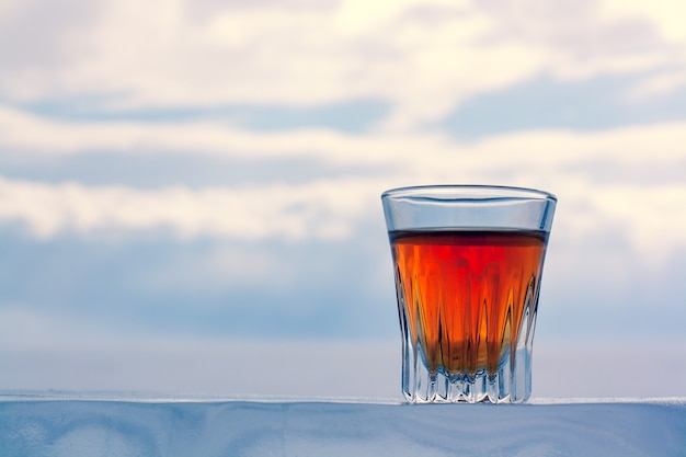 A beautiful glass of alcohol stands on an icy base against the sky. chilled whiskey outdoors in winter. orange drink in a glass. copy space. side view. horizontal.