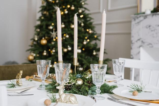 Красивые стеклянные бокалы, свечи в декоре праздничного стола. сервировка рождественского стола