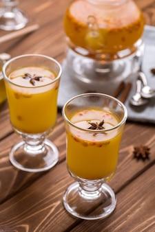 オレンジ色のシーバックソーンティーと美しいガラスのティーポット。暑い冬の飲み物
