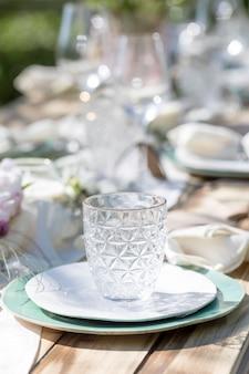 昼食のためのテーブルの上のセラミックプレート上の美しいガラスの花瓶