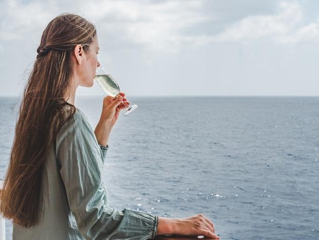 바다 파도 태양 광선의 배경에 음료와 함께 아름 다운 유리. 상위 뷰, 클로즈업. 여가와 여행의 개념