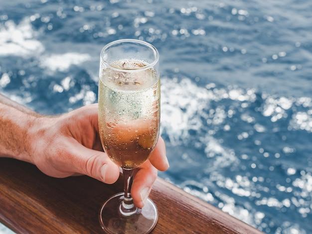 Красивый бокал с напитком на фоне морских волн