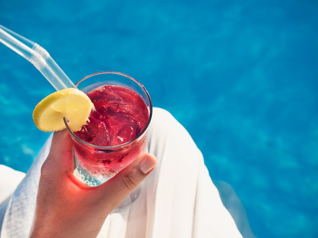 Beautiful glass with a cocktail on the background of the pool. top view