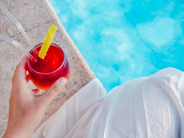 Beautiful glass with a cocktail in the swimming pool. top view