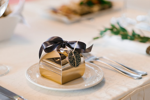 A beautiful gold foil box with a brown satin bow on it, a wedding bonbonniere, on a white serving plate on the banquet table