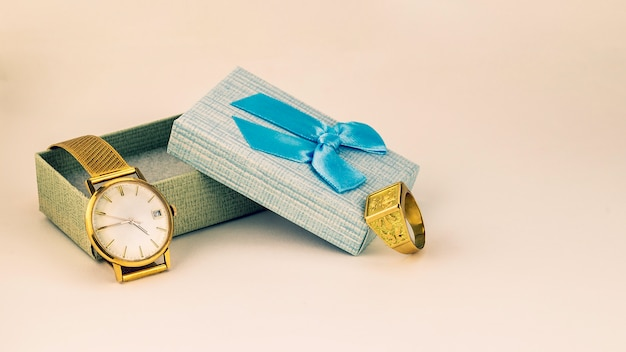 Beautiful gold watch and ring in gift box with blue ribbon