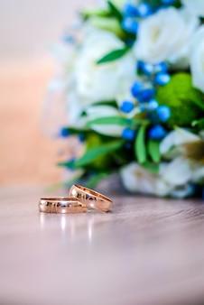 Красивые золотые обручальные кольца на столе рядом с букетом невесты из белых и синих цветов