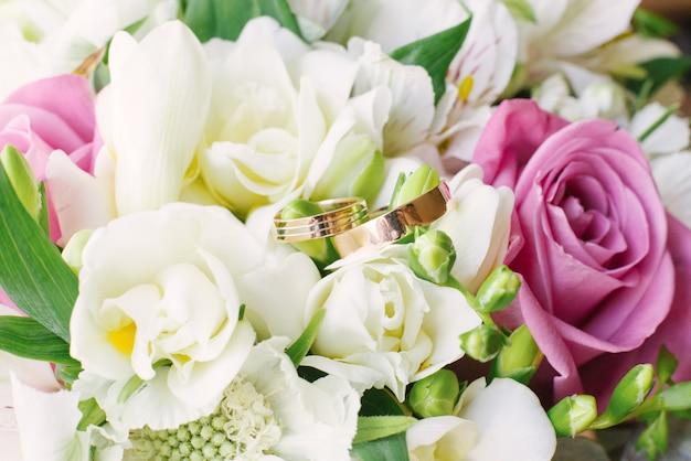 Beautiful gold wedding rings on a wedding bouquet