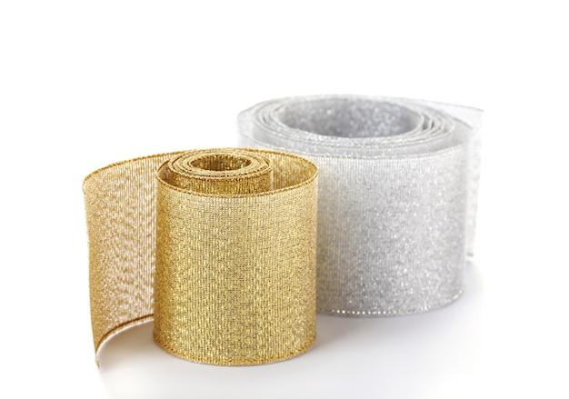 白い表面に分離された美しい金と銀のリボン