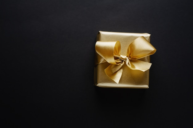 Beautiful golden box christmas gift with golden ribbon on black.