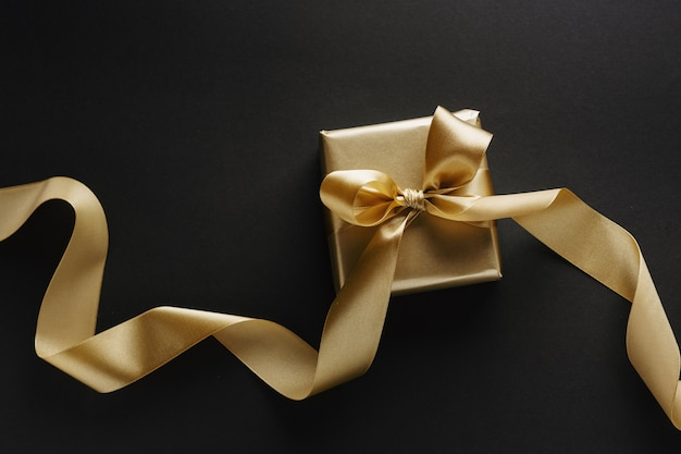Beautiful golden box christmas gift with golden ribbon on black