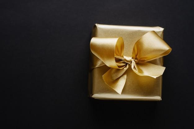 어둠에 황금 리본으로 아름 다운 황금 상자 크리스마스 선물.