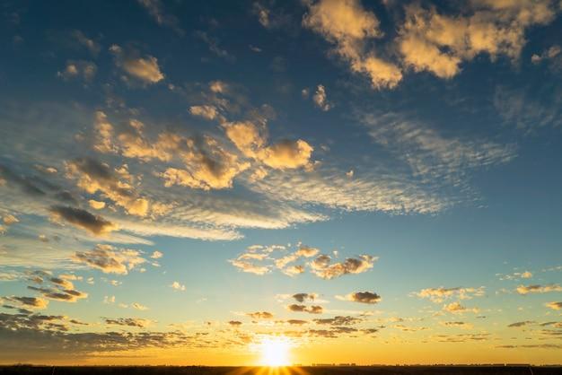 Красивые золотые облака, освещенные лучами солнца на закате, плывут по желто-голубому небу.