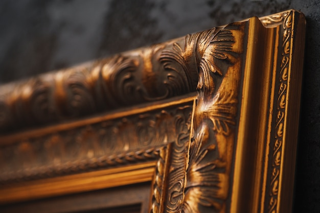 Beautiful golden frame on black wall with pattern close up