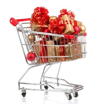 Красивые золотые подарки с красной лентой и елочными шарами в корзине, изолированной на белом