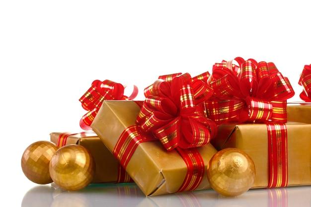 Красивые золотые подарки с красной лентой и елочными шарами, изолированными на белом