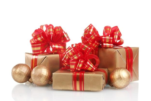 Красивые золотые подарки с красной лентой и елочными шарами, изолированные на белом