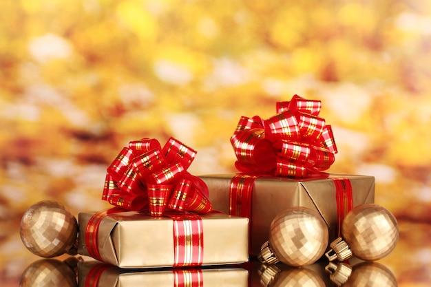 Красивые золотые подарки с красной лентой и елочными шарами на желтом фоне