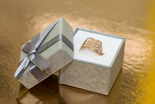 Beautiful golden jewellery in gift box on golden wall