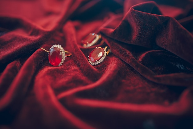 Beautiful golden jewelry with jem on red velvet background